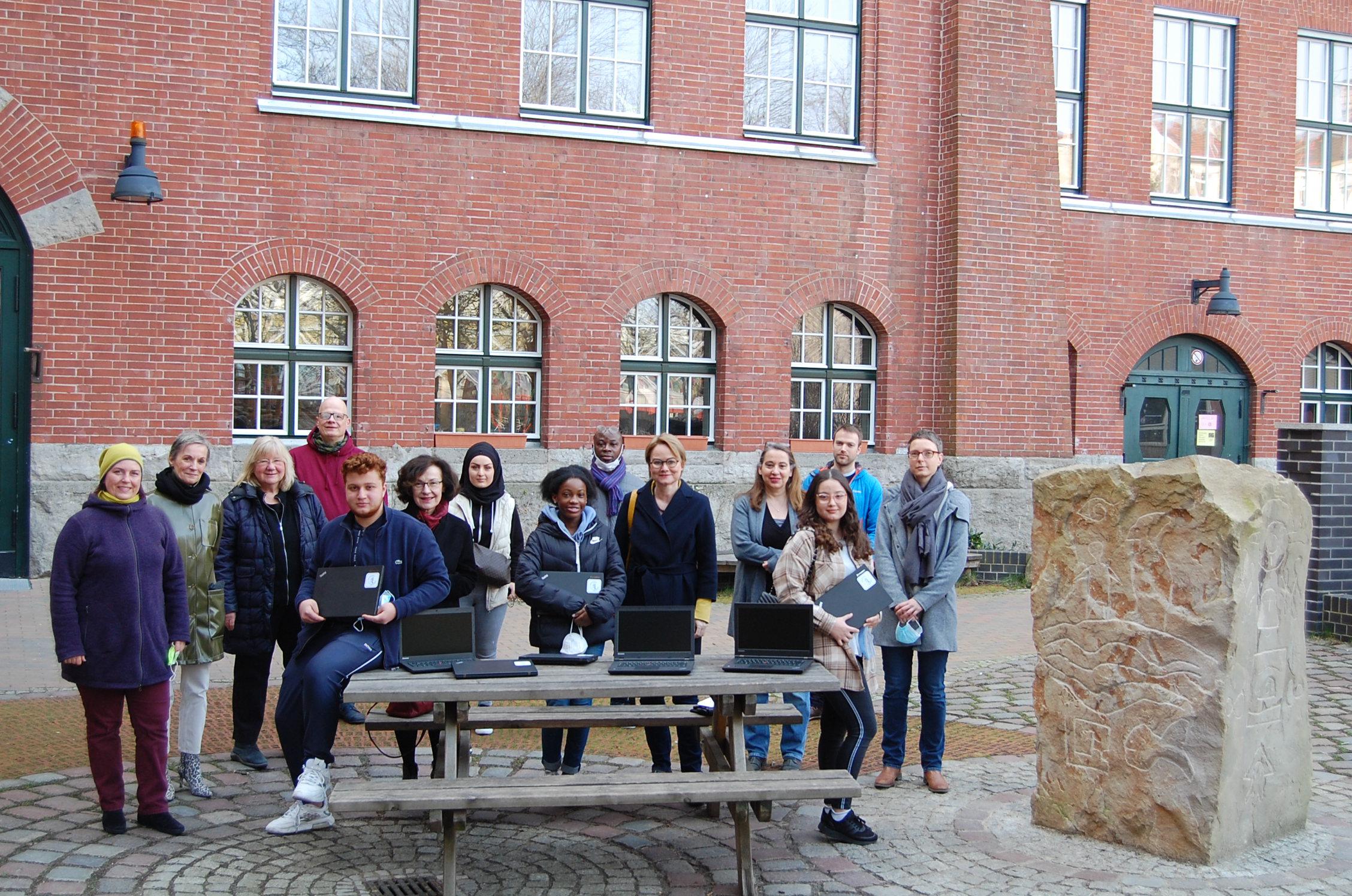 SchülerInnen, LehrerInnen, Vertreterinnen der Soroptimisten und der Förderverein mit Laptops vor der Paula-Fürst-Gemeinschaftsschule